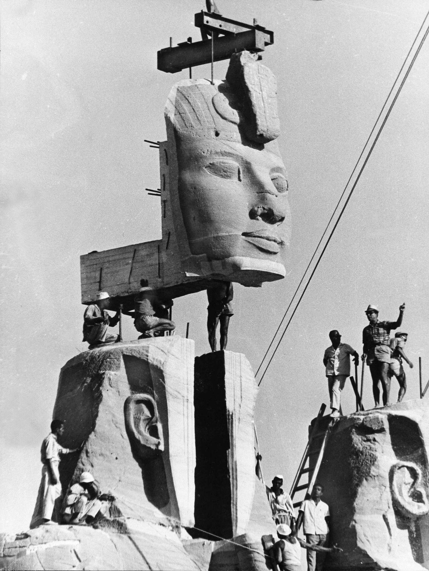 FILE - In this photo taken on Oct. 11, 1966 in Egypt, workmen lower one of the heads of the four rock-hewn colossi of King Ramses II into place, on the foundation of the re-sited monument. The global campaign that saved the ancient Egyptian temples of Abu Simbel from inundation by the Aswan Dam 50 years ago was remembered this week as an unprecedented engineering achievement and a turning point in the perception of cultural treasures as a responsibility of all humanity. (AP Photo)