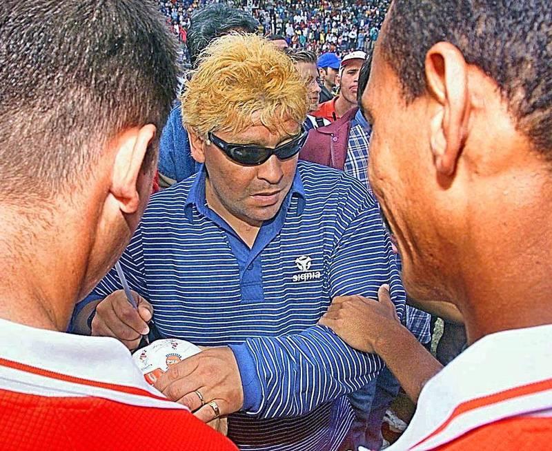 """Argentine ex-soccer player Diego Armando Maradona (C) signs autographs in Havana 06 February 2000. El exfutbolista argentino Diego Armando Maradona (C, con gafas) firma autografos a admiradores en el Estadio Pedro Marrero de La Habana, el 06 de febrero de 2000. Maradona participa en  el juego final del campeonato de futbol cubano, entre los equipos de Ciudad de La Habana y Pinar del Rio. Maradona fue declarado """"activista del futbol cubano"""". (ELECTRONIC IMAGE) (Photo by ADALBERTO ROQUE / AFP)"""