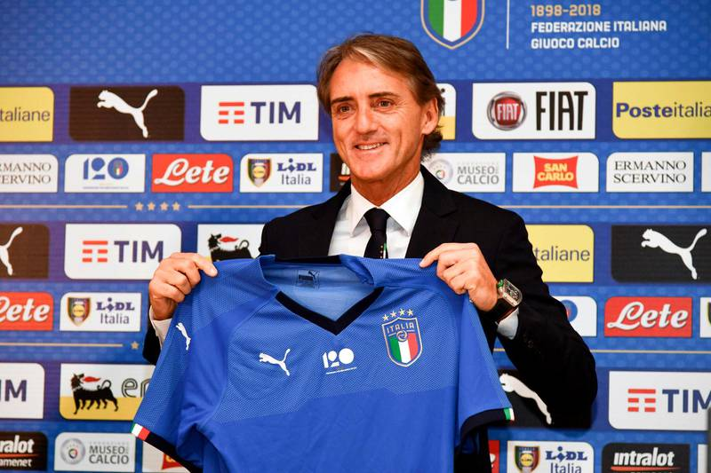 Italy's national football team newly appointed head coach, Roberto Mancini holds Italy's jersey during a press conference on May 15, 2018 at the national team's training centre at Coverciano near Florence.  Italy head coach has the task of reviving Azzurri fortunes six months after their shock failure to qualify for the World Cup 2018 in Russia. Italy have been without a permanent coach since Gian Piero Ventura was sacked after the four-time world champions failed to qualify for the World Cup for the first time since 1958.  / AFP / Carlo BRESSAN