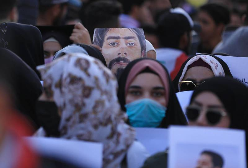 Iraqi demonstrators hold up a portrait of late fellow protester Safaa Saray, killed during the past three months of anti-government protests, as thousands took to the streets on January 10, 2020 in the Shiite holy city of Karbala in central Iraq and other cities across the country,  reviving the opposition movement against the authorities and adding criticisms of both the US and Iran to their chants. The anti-regime rallies had been overshadowed recently by spiralling tensions between Tehran and Washington, which led each country to carry out strikes against the other's assets in Iraq over the last week. / AFP / Mohammed SAWAF