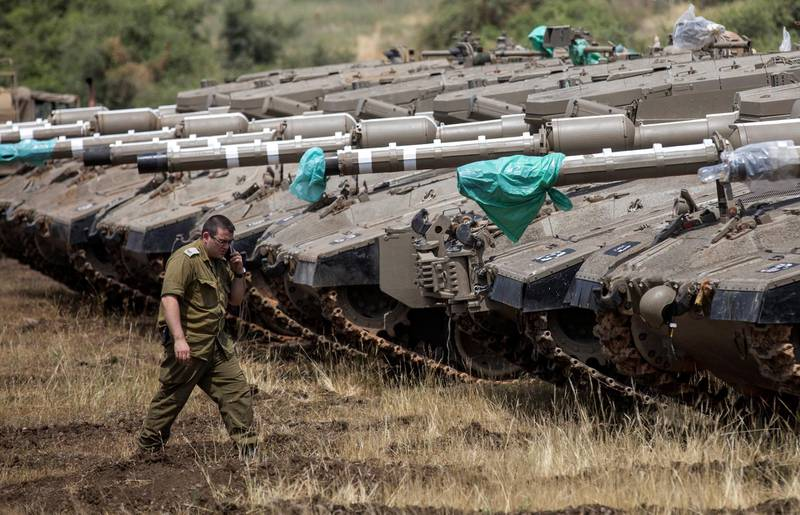 epa06722690 An Israeli soldier walks next to Merkava tanks deployed near the Israeli-Syrian border in the Golan Heights, 09 May 2018. Tensions have increased between Israel and Syria after Damascus accused Israel of carrying air strikes against a missile base south of its capital, resulting in two Israeli missiles being shot down by Syrian air defenses in the Kiswah area on 08 May, media reported. Israel has alleged that 'irregular Iranian activity' was detected in the occupied Golan Heights.  EPA/ATEF SAFADI