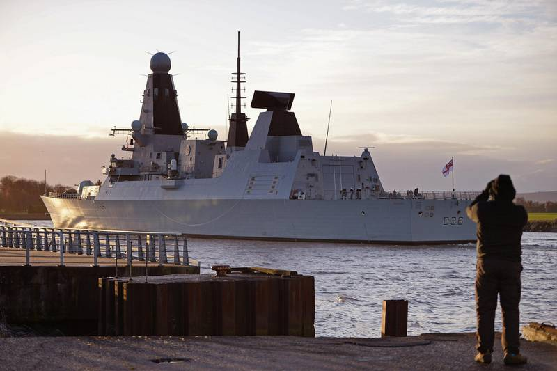 GLASGOW, SCOTLAND - NOVEMBER 29:  An onlooker watches as HMS Defender makes its way up the River Clyde on November 29, 2013 in Glasgow, Scotland. HMS Defender is one of the Royal Navy's new Type 45 destroyers, and has returned to Glasgow where it was built for the first time since becoming a fully fledged member of the fleet and will be open to the public tomorrow.  (Photo by Jeff J Mitchell/Getty Images)