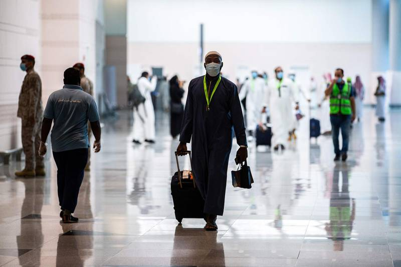 """A handout picture provided by the Saudi Ministry of Hajj and Umra on July 25, 2020, shows a traveller, mask-clad due to the COVID-19 coronavirus pandemic, walking with his luggage as part of the first group of arrivals for the annual Hajj pilgrimage, at the Red Sea coastal city of Jeddah's King Abdulaziz International Airport. The 2020 hajj season, which has been scaled back dramatically to include only around 1,000 Muslim pilgrims as Saudi Arabia battles a coronavirus surge, is set to begin on July 29. Some 2.5 million people from all over the world usually participate in the ritual that takes place over several days, centred on the holy city of Mecca. This year's hajj will be held under strict hygiene protocols, with access limited to pilgrims under 65 years old and without any chronic illnesses. - === RESTRICTED TO EDITORIAL USE - MANDATORY CREDIT """"AFP PHOTO / HO / MINISTRY OF HAJJ AND UMRA"""" - NO MARKETING NO ADVERTISING CAMPAIGNS - DISTRIBUTED AS A SERVICE TO CLIENTS ===  / AFP / Saudi Ministry of Hajj and Umra / - / === RESTRICTED TO EDITORIAL USE - MANDATORY CREDIT """"AFP PHOTO / HO / MINISTRY OF HAJJ AND UMRA"""" - NO MARKETING NO ADVERTISING CAMPAIGNS - DISTRIBUTED AS A SERVICE TO CLIENTS ==="""