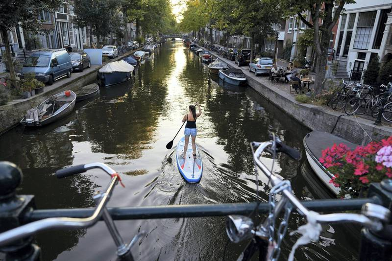 AMSTERDAM, NETHERLANDS - SEPTEMBER 21: A woman is padding on a canal on September 21, 2020 in Amsterdam, Netherlands. Due to the rapid rise in new Coronavirus cases, Dutch authorities have imposed a 1 a.m. curfew on bars and restaurants in Amsterdam and other major cities. The Netherlands has reported some 90,047 coronavirus cases, with 2000 new recorded cases in the last 24 hours.  (Photo by Pierre Crom/Getty Images)