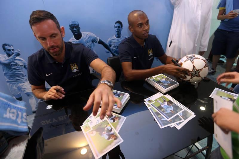 November 15, 2013 (Abu Dhabi) Manchester City footballers Feenandinho and Richard Wright sign autographs at the City Store at Marina Mall in Abu Dhabi November 15, 2013. (Sammy Dallal / The National)  *** Local Caption ***  sd-111613-football-06.jpg