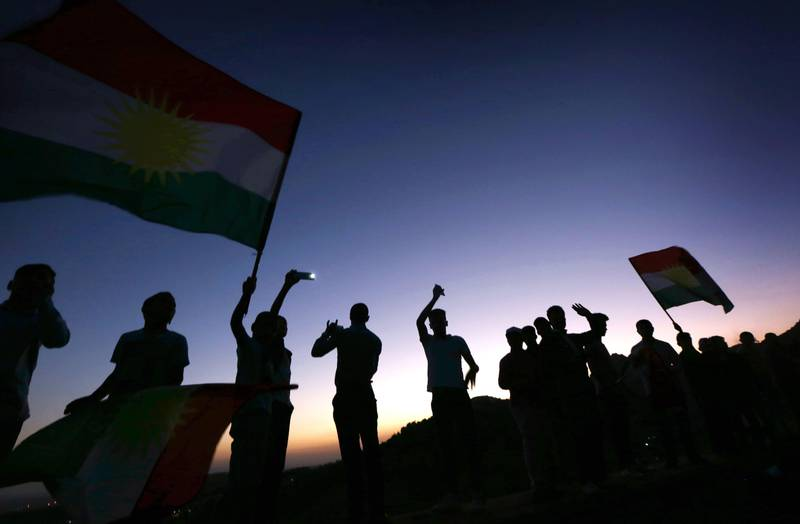 TOPSHOT - Iraqi Kurds wave Kurdish flags during a gathering to show support for the upcoming independence referendum and encourage people to vote in the town of Akra, some 500 kilometres north of Baghdad on September 10, 2017.  Iraq's autonomous Kurdish region will hold a historic referendum on statehood in September 2017, despite opposition to independence from Baghdad and possibly beyond. / AFP PHOTO / SAFIN HAMED