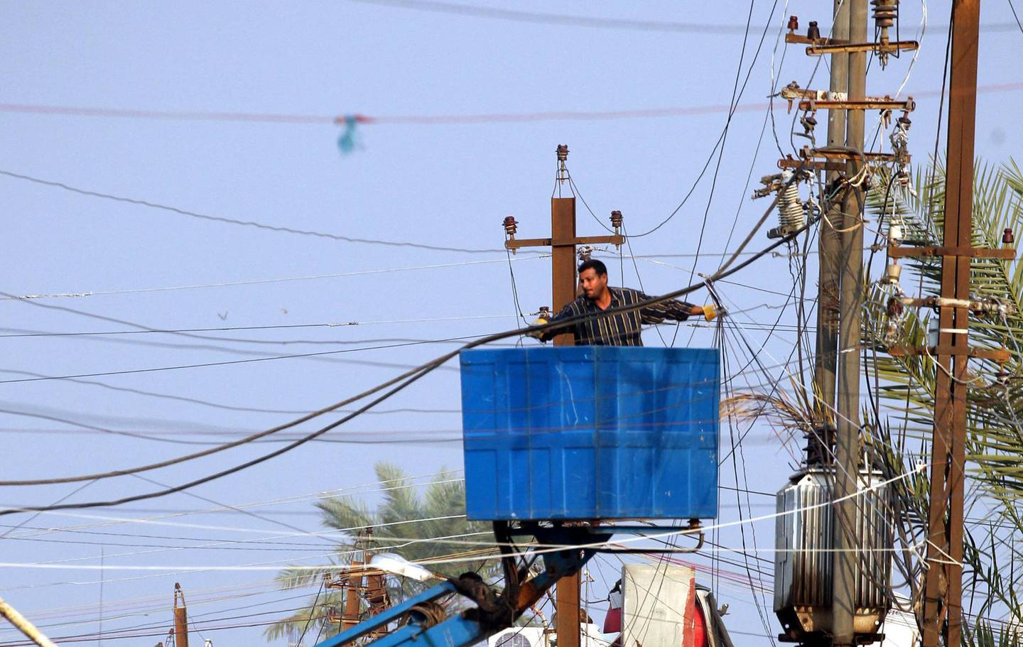 A maintenance worker repairs power lines, cut due to heavy rainfall, in the Iraqi capital Baghdad, on November 23, 2013. Flooding and heavy rain across Iraq has caused widespread structural damage across the country. AFP PHOTO/SABAH ARAR (Photo by SABAH ARAR / AFP)