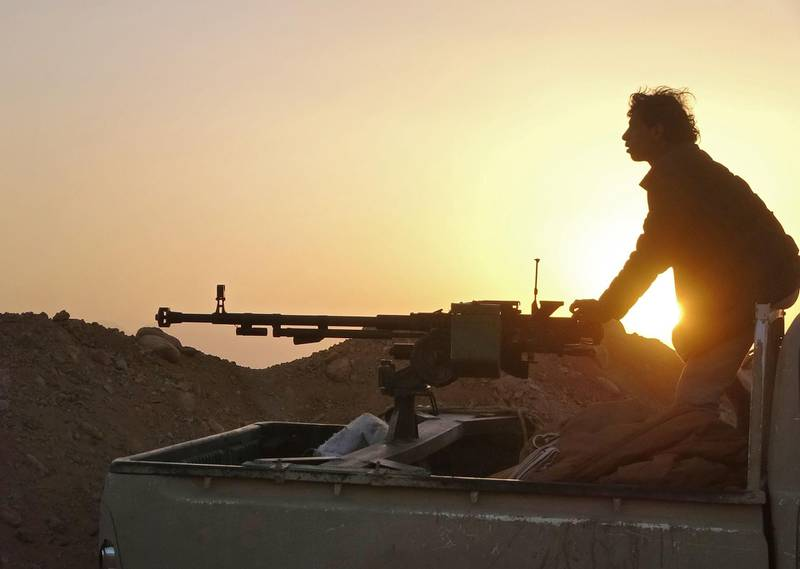 """(FILES) In this file photo a combatant mans a heavy machine gun as forces loyal to Yemen's Saudi-backed government clash with Huthi rebel fighters around the strategic government-held """"Mas Camp"""" military base, in al-Jadaan area about 50 kilometres northwest of Marib in central Yemen, on November 22, 2020.  Key US lawmakers on January 11, 2021 urged a quick reversal of outgoing Secretary of State Mike Pompeo's branding of Yemen's Huthis as a terrorist group, saying he had worsened a humanitarian crisis. """"The designation of the Huthis as a terrorist organization is a death sentence for thousands of Yemenis"""", said Senator Chris Murphy, a prominent member of President-elect Biden's Democratic Party. """"It will cut off humanitarian aid, make peace talks nearly impossible and empower Iran. Biden should reverse this policy on day one,"""" he wrote on Twitter.  / AFP / -"""