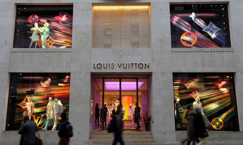 FILE -  In this Monday, Nov. 25, 2019 file photo, pedestrians pass a Louis Vuitton shop window in London. Sales of luxury apparel, jewelry and beauty products are set to slide by nearly a quarter this year as the pandemic wipes out more than six years of growth, according to a study released Wednesday, Nov. 18, 2020 by the consultancy Bain. (AP Photo/Kirsty Wigglesworth, File)