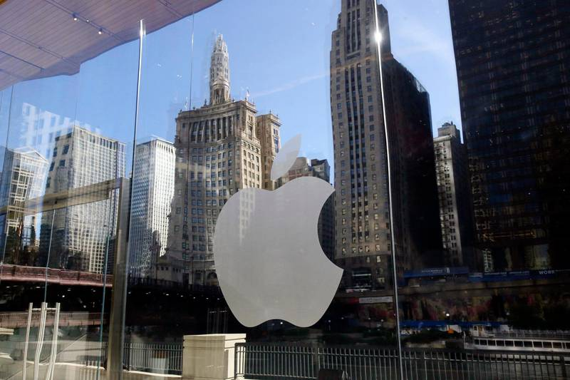 FILE - In this Thursday, Oct. 19, 2017, file photo, buildings are reflected behind the logo at an Apple Store in downtown Chicago. Apple Music is coming to a city near you — the streaming service launched daily music charts focused on particular cities around the world on Monday, April 26, 2021. (AP Photo/Kiichiro Sato, File)