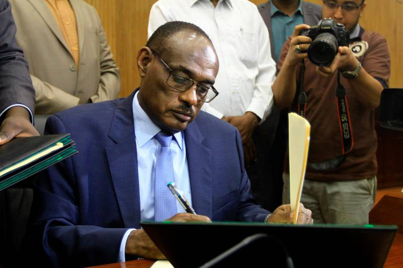 """Sudanese Foreign Minister Ahmed al-Dierdiry signs a """"preliminary"""" power-sharing deal between South Sudanese arch-foes, on July 25, 2018, in Khartoum. South Sudanese arch-foes signed a """"preliminary"""" power-sharing deal aimed at ending the civil war, with a Sudanese minister saying it sees rebel leader Riek Machar reinstated as first vice president. / AFP / Ebrahim Hamid"""