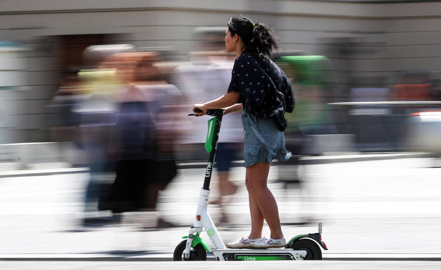 epa07724873 A woman rides on an electric scooter in Berlin, Germany, 18 July 2019. The shared electric scooters have been allowed to circulate in the capital since 15 June 2019. Multiple companies offer this service with a wide range of units parked around the city.  EPA/FELIPE TRUEBA