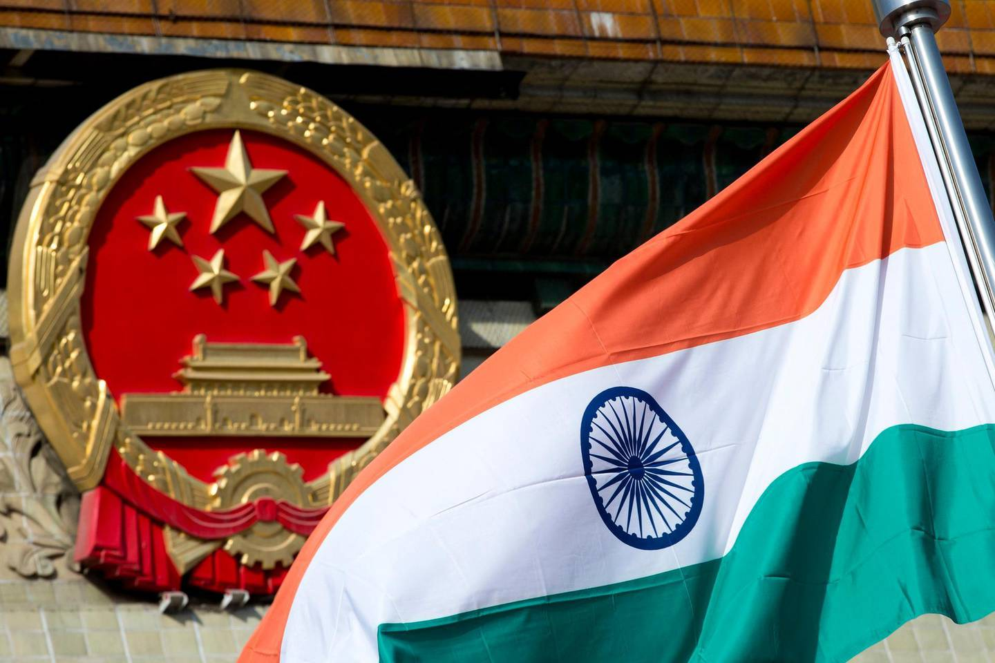 FILE - In this Oct. 23, 2013, file photo, an Indian national flag is flown next to the Chinese national emblem outside the Great Hall of the People in Beijing. China's Commerce Ministry said Thursday, Aug. 13, 2020 it has extended punitive tariffs on Indian optical fiber products for five years. The announcement follows a yearlong review after a previous tariff expired in 2019. It takes effect Aug. 14. (AP Photo/Andy Wong, file)