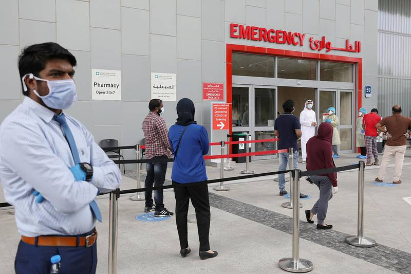 People wearing protective face masks wait to be tested, amid the coronavirus disease (COVID-19) outbreak, at the Cleveland Clinic hospital in Abu Dhabi, United Arab Emirates, April 20, 2020. Picture taken April 20, 2020. REUTERS/Christopher Pike