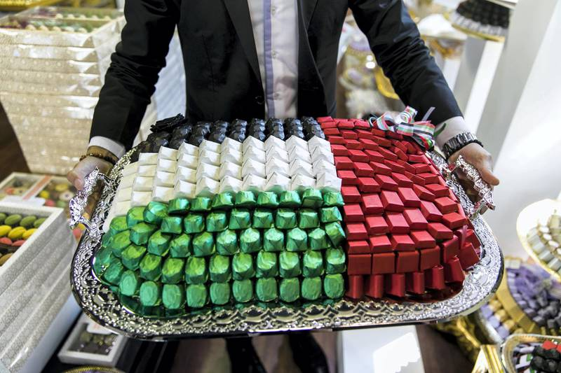 ABU DHABI, UNITED ARAB EMIRATES - NOV 1:Abdulaziz Diag, Morrrocan, 29, shows the offer UAE flag themed chocolate options available at the store he manages, Chocolate Boutique.(Photo by Reem Mohammed/The National)Reporter: Anna ZachariasSection: NA