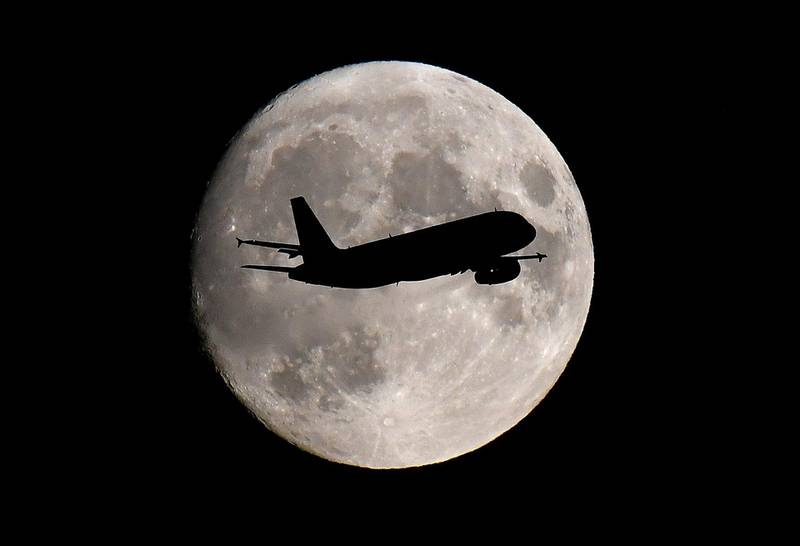 FILE PHOTO: A passenger plane passes in front of the moon as it makes its final landing approach to Heathrow Airport in London, Britain September 12, 2019. REUTERS/Toby Melville/File Photo