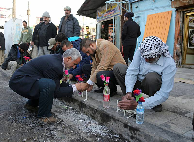 People light candles at the site of Monday's twin suicide bombings in Baghdad, Iraq, Tuesday, Jan. 16, 2018. Two suicide bombers blew themselves up at a busy street market in central Baghdad on Monday, in back-to-back explosions that killed dozens and wounded many civilians, Iraqi health and police officials said. It was the deadliest attack since last month's declaration of victory over the Islamic State group. (AP Photo/Karim Kadim)