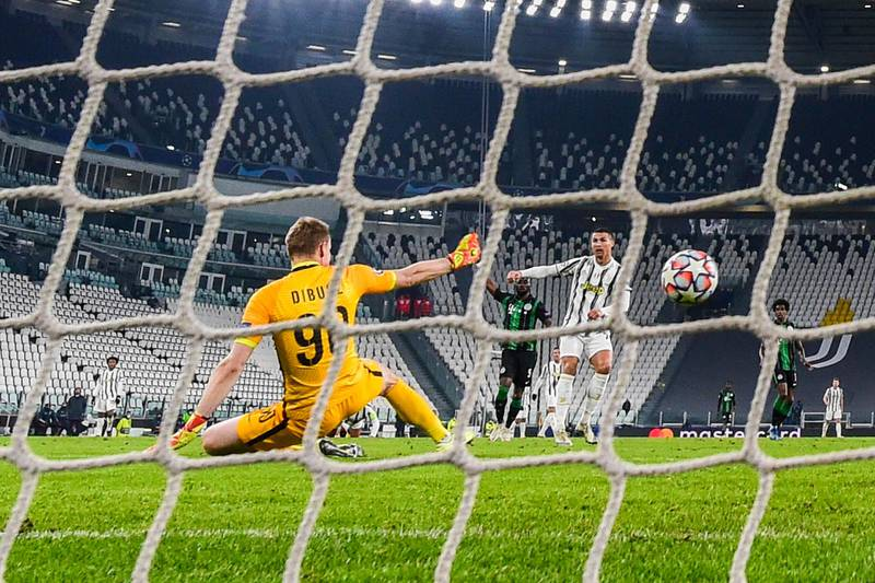Juventus' Portuguese forward Cristiano Ronaldo (R) sccores an equalizer past Ferencvaros' Hungarian goalkeeper Denes Disbusz (L) during the UEFA Champions League Group G football match Juventus vs Ferencvaros on November 24, 2020 at the Juventus stadium in Turin. (Photo by Miguel MEDINA / AFP)