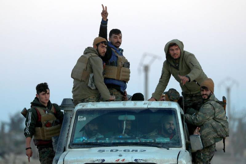 This picture shows members of the Syrian Democratic Forces (SDF) in Hajin, in the Deir Ezzor province, eastern Syria, on December 15, 2018. Kurdish-led forces seized the Islamic State's main hub of Hajin on December 14, a milestone in a massive and costly US-backed operation to eradicate the jihadists from eastern Syria. The Syrian Democratic Forces secured Hajin, the largest settlement in what is the last pocket of territory controlled by IS, the Syrian Observatory for Human Rights said. / AFP / Delil SOULEIMAN