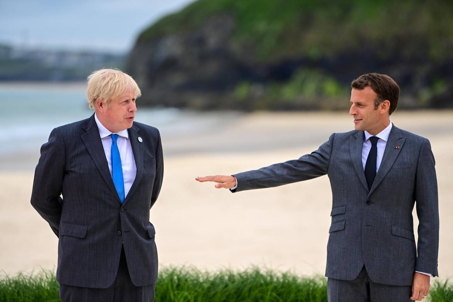Emmanuel Macron, France's president, right, gestures to Boris Johnson, U.K. prime minister, on the first day of the Group of Seven leaders summit in Carbis Bay, U.K., on Friday, June 11, 2021. U.K. Prime Minister Boris Johnson will give leaders a beachside welcome, formally kicking off three days of summitry along the English coast after meeting U.S. President Joe Biden for the first time on Thursday.  Photographer: Neil Hall/EPA/Bloomberg