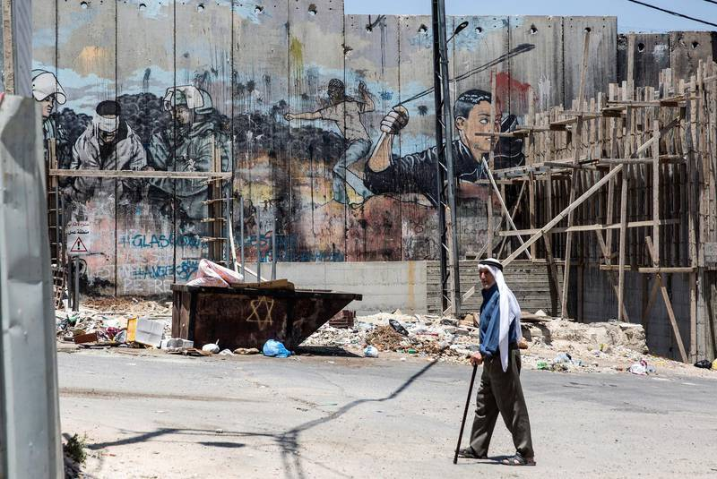 Palestinian Abdel Hadeef Abu Sul,87, walks along Israel's separation camp near his home in the Aida refugee camp in the city of Bethlehem on June 23,2019 .Photo by Heidi Levine for The National