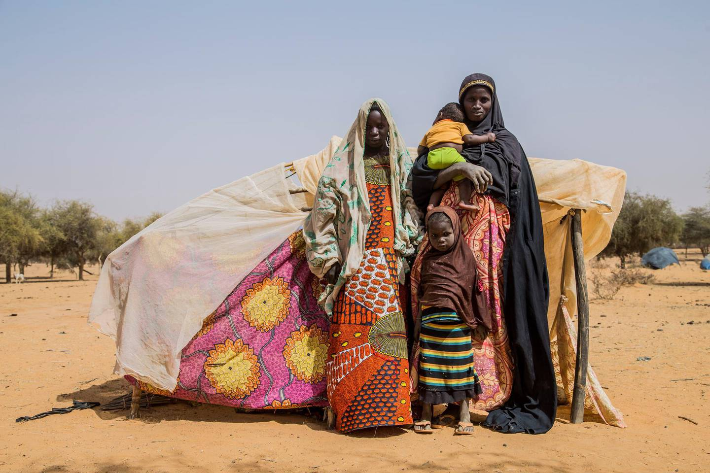 6. MaliAigachatou, a single mother and her children, standing in front of their makeshift tent after fleeing violence in Timbuktu in Mali.Photo: Togo Moise/NRC