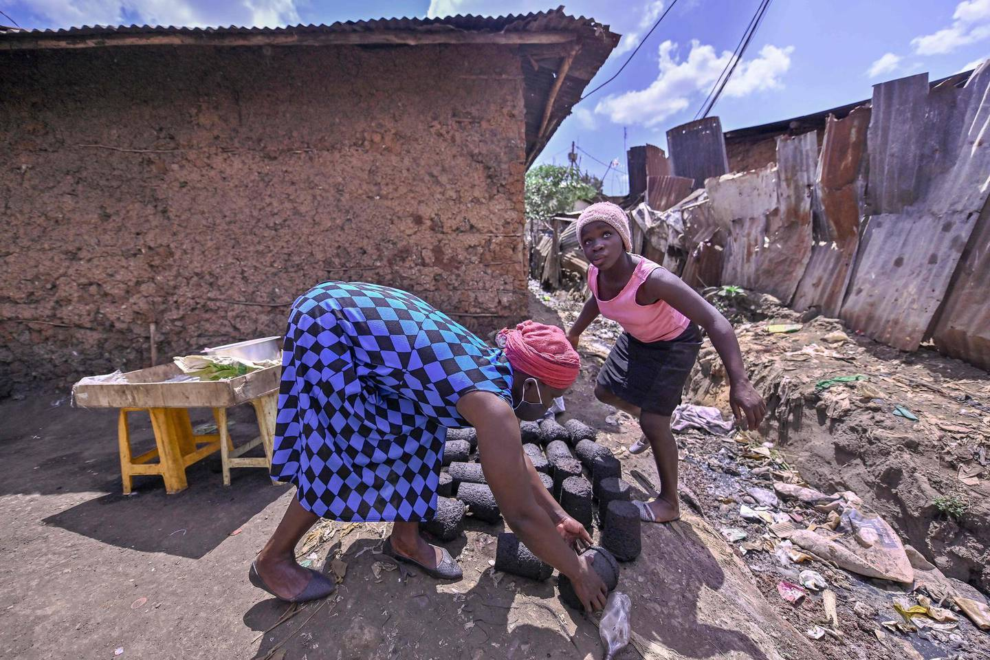Bella Achieng (R), works with her mother Lilian Adhiambo at her open-air groceries stand near their home in Kibera slum, in Nairobi, on August 7, 2020, as schools remain closed across the country following a government directive as a measure to stem the spread of the COVID-19 (novel coronavirus). Achieng is a student at Kibera School for Girls that is run by Kenya-based charity Shining Hope for Communities (SHOFCO) where needy students from the surrounding slum who are facing challenges at home with access to the internet for virtual learning are permitted to study at the premises in order to access the wi-fi. Many private primary and secondary schools continue offering virtual lessons to their students at home. This is however a challenge for others who cannot afford a smart phone or daily data costs. / AFP / TONY KARUMBA