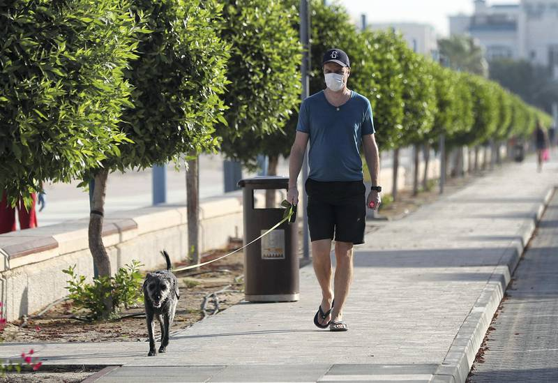 Dubai, United Arab Emirates - Reporter: N/A: Coronavirus. A man walks his dog by the beach on the first morning where the government has eased restrictions on personal travel due to Covid-19. Friday, April 24th, 2020. Dubai. Chris Whiteoak / The National