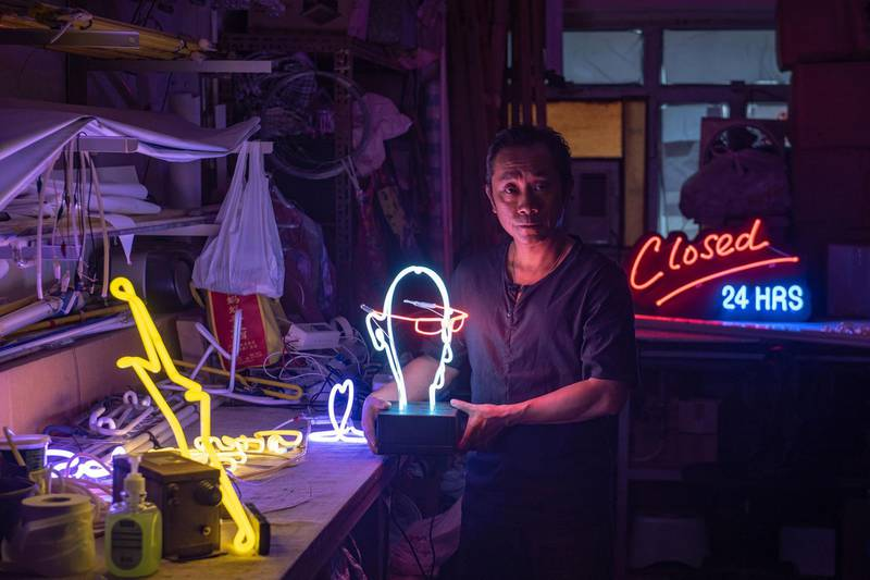 In this picture taken on April 16, 2018, neon sign maker Wu Chi-kai poses during an interview with AFP in Hong Kong. Neon sign maker Wu Chi-kai is one of the last remaining craftsmen of his kind in Hong Kong, a city where darkness never really falls thanks to the 24-hour glow of a myriad lights.  Ahead of May Day, AFP's video and photo teams spoke to men and women around the globe whose jobs are becoming increasingly rare, particularly as technology transforms societies. / AFP PHOTO / Philip FONG / PHOTO ESSAY ON 'DISAPPEARING JOBS' MORE PHOTOS AVAILABLE ON AFPFORUM.COM
