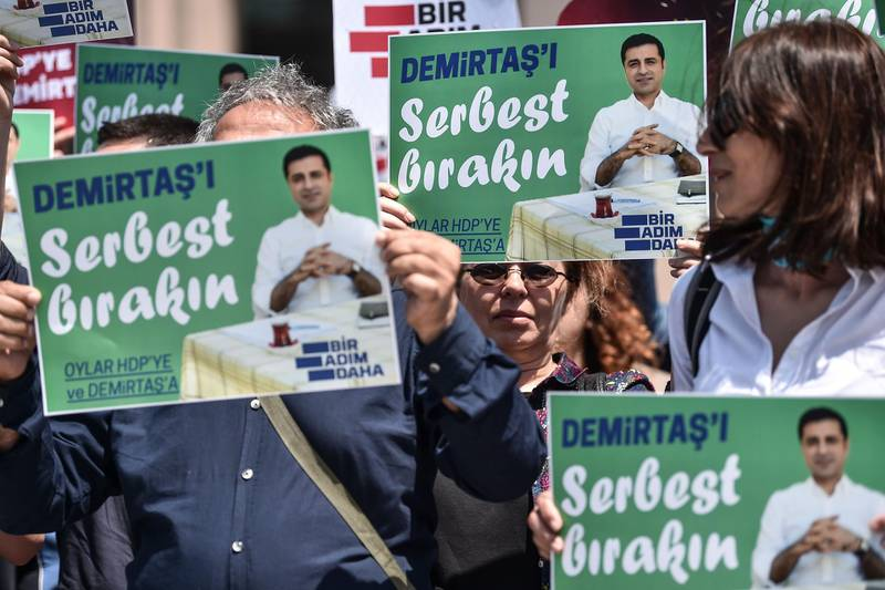 """Supporters of the Peoples' Democratic Party (HDP) hold placards reading """"Free Demirtas"""" in front of Istanbul's Courthouse on May 21, 2018, to demand the release of Pro-Kurdish party leader Selahattin Demirtas who is currently in a Turkish jail. Turkey's jailed former pro-Kurdish party leader Selahattin Demirtas, 45, who is running against the Turkish President in the June 24 polls despite being held in jail for the last one-and-a-half years, lambasted the """"unfairness"""" of his campaign conditions, but said he was ready to rally voters from prison. / AFP / OZAN KOSE"""