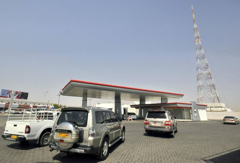 Cars line up at a petrol station in Al Buraimi, near Oman's border with the United Arab Emirates September 14, 2010. Gasoline price hikes in the United Arab Emirates have boosted sales in neighbouring Oman this year as motorists cross the border to fill up on cheaper fuel, and some have begun to resell it to UAE firms. UAE gasoline prices have risen 26 percent since April, when the government introduced the first of two price hikes imposed so far. Neighbouring Oman has kept its fuel subsidies unchanged.  This station has experienced an increase of up to fifty percent in sales since the rise in fuel prices in the UAE, according to the owner. Picture taken September 14, 2010. REUTERS/Jumana El-Heloueh (OMAN - Tags: TRANSPORT BUSINESS)