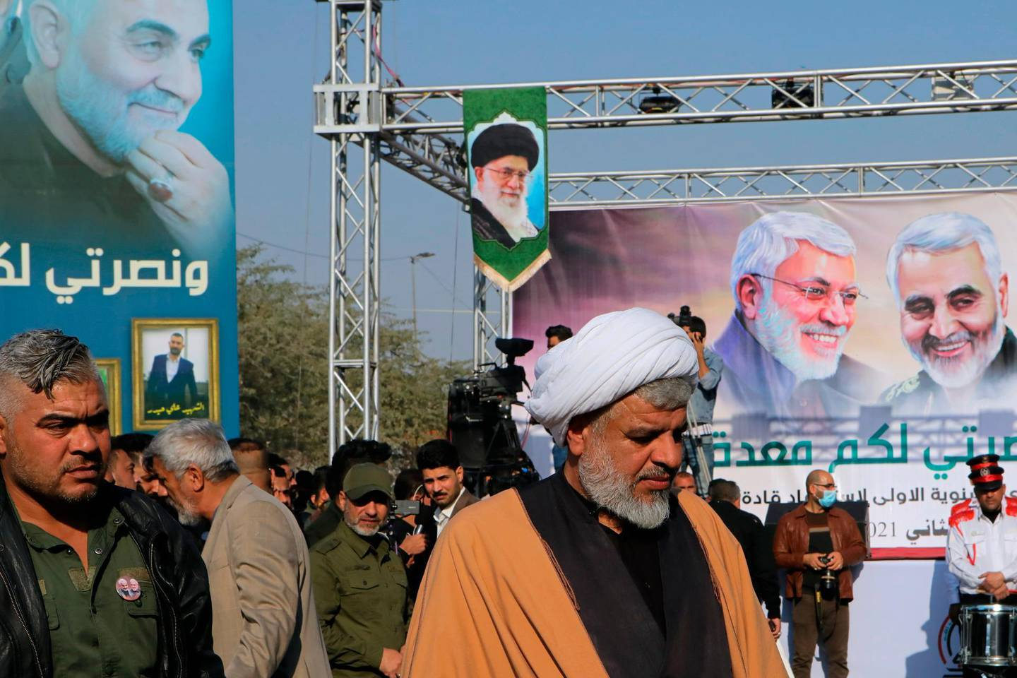 Supporters of the Popular Mobilization Forces hold a poster of Supreme Leader Ayatollah Ali Khamenei, center, and Abu Mahdi al-Muhandis, deputy commander of the Popular Mobilization Forces and General Qassem Soleimani, head of Iran's Quds force during a rally to commemorate the anniversary of the killing of Soleimanil and al-Muhandis in a U.S. drone strike in Basra, Iraq, Friday, Jan. 8, 2021. (AP Photo/Nabil al-Jurani)