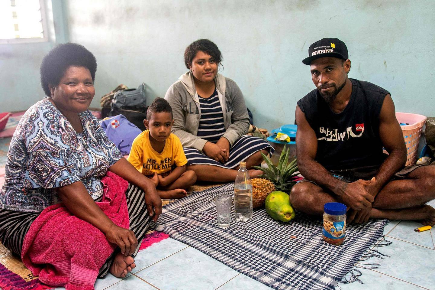 A Fijian family takes refuge in a temporary shelter from the strong damaging winds in the capital city of Suva on December 17, 2020.   Fijians were warned that no part of the Pacific island nation would escape the wrath of approaching super cyclone Yasa, expected to bring flash floods, huge waves and widespread destruction. / AFP / Leon LORD