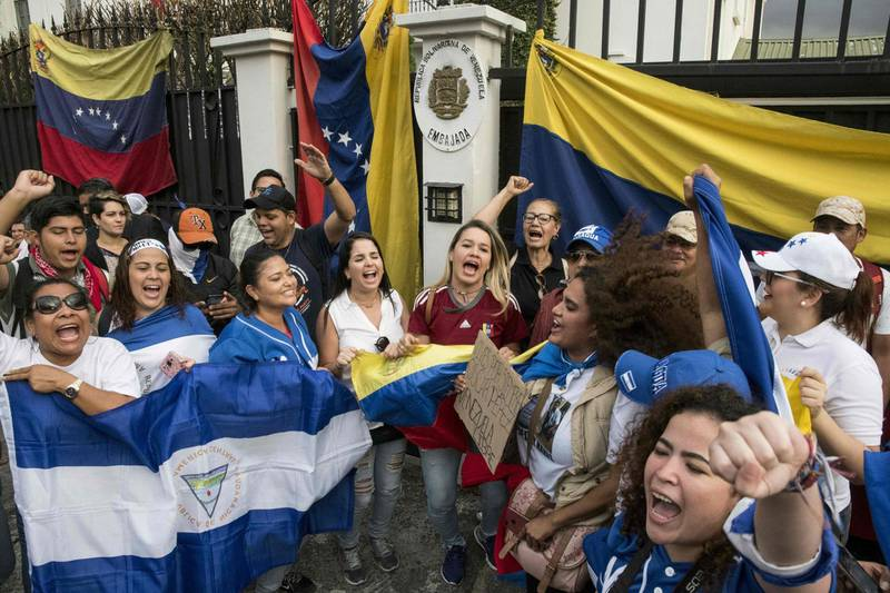 Venezuelan citizens protest against Venezuelan President Nicolas Maduro outside the Venezuelan embassy in San Jose, on April 30, 2019.  Venezuelan opposition chief Juan Guaido declared himself acting president in January 2019 and claimed on April 30 to have also secured the backing of Venezuelan soldiers, while the country's leftist government said an attempted coup was under way. / AFP / Ezequiel BECERRA