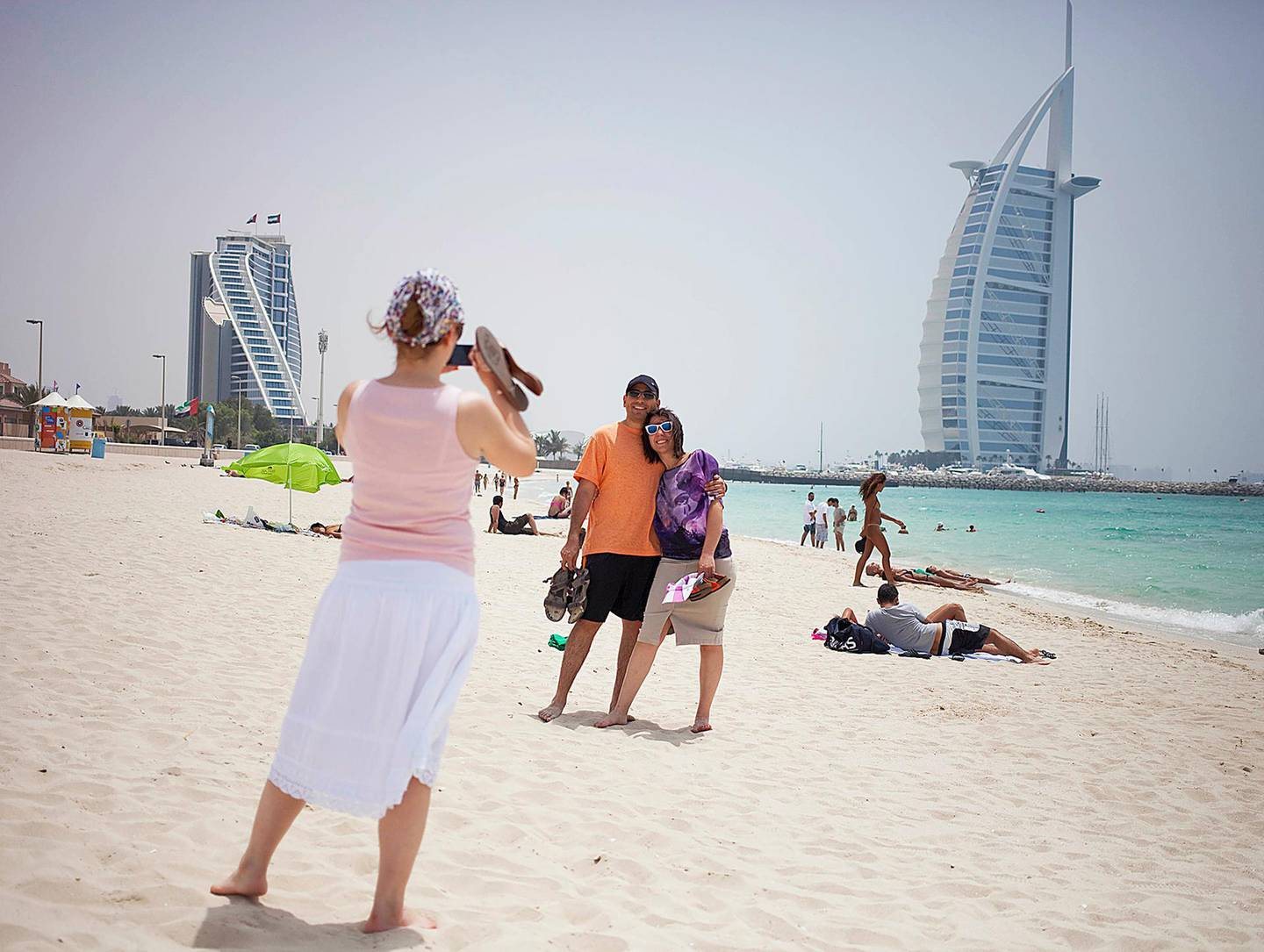 Dubai, United Arab Emirates - May 23 2013 - Tourists from Turkey take pictures at the public beach by Burj Al Arab after being dropped off there by a tour bus. STOCK. (Razan Alzayani / The National)