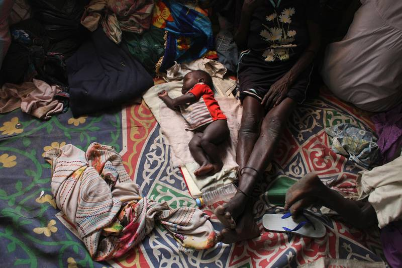 A baby sleeps next to a woman in a Catholic church in Malakal January 21, 2014. According to the people at the church, there are some 6,000 internally displaced people taking refuge at the church.  REUTERS/Andreea Campeanu  (SOUTH SUDAN - Tags: CIVIL UNREST POLITICS CONFLICT TPX IMAGES OF THE DAY)