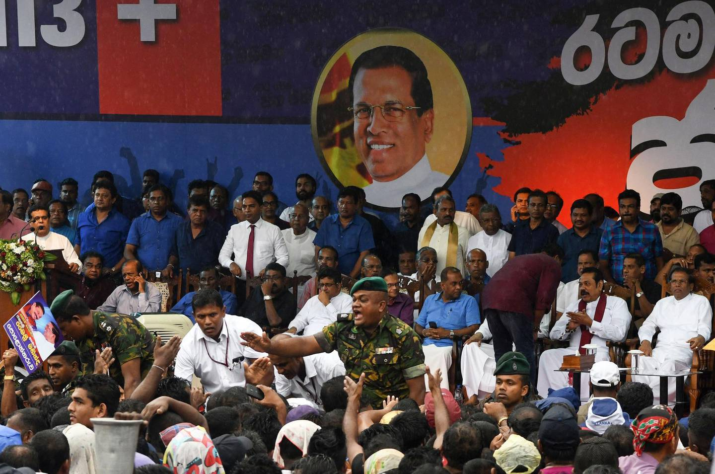 Sri Lankan police officer tries to control supporters of Sri Lanka's former president and newly appointed prime minister Mahinda Rajapakse and President Maithripala Sirisena at a rally in Colombo on November 5, 2018. Thousands of supporters of former Sri Lankan president Mahinda Rajapakse headed for the capital on November 5 to rally in support of his controversial nomination as prime minister, as the island's constitutional crisis deepened.  / AFP / LAKRUWAN WANNIARACHCHI
