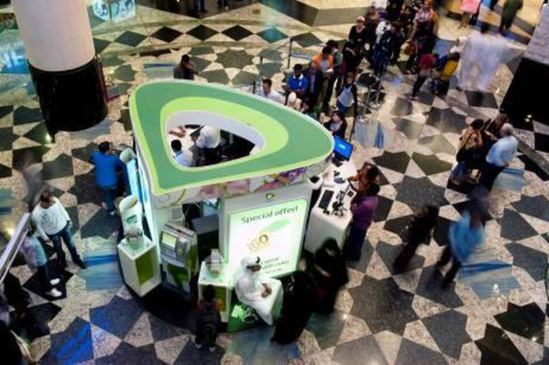 Dubai, United Arab Emirates - Dec 29, 2011 - Shoppers line up at the Etisalat stall at Mall of the Emirates in Dubai. Sarah Dea / The National