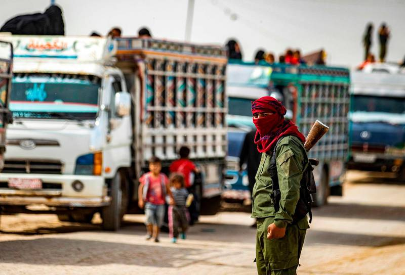 A Kurdish fighter stands in front of a convoy of trucks at the Kurdish-run al-Hol camp, transporting women and children suspected of being related to Islamic State (IS) group, after being released from the camp to return to their homes, in the al-Hasakeh governorate in northeastern Syria, on October 28, 2020.   / AFP / Delil SOULEIMAN