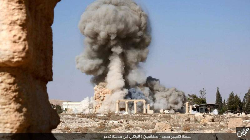 """An undated image, which appears to be a screenshot from a video and which was published by the Islamic State group in the Homs province (Welayat Homs) on August 25, 2015, allegedly shows smoke billowing from the Baal Shamin temple in Syria's ancient city of Palmyra. The temple was reportedly destroyed by the extremist group and news of its demolition sparked international condemnation earlier this week. AFP PHOTO / HO / WELAYAT HOMS  === RESTRICTED TO EDITORIAL USE - MANDATORY CREDIT """"AFP PHOTO / HO / WELAYAT HOMS"""" - NO MARKETING NO ADVERTISING CAMPAIGNS - DISTRIBUTED AS A SERVICE TO CLIENTS FROM ALTERNATIVE SOURCES, AFP IS NOT RESPONSIBLE FOR ANY DIGITAL ALTERATIONS TO THE PICTURE'S EDITORIAL CONTENT, DATE AND LOCATION WHICH CANNOT BE INDEPENDENTLY VERIFIED === (Photo by - / WELAYAT HOMS / AFP)"""