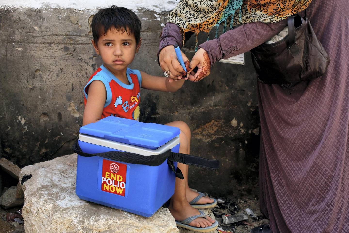 A boy gets his finger marked, after he is administered polio vaccine drops, during an anti-polio campaign, in a low-income neighbourhood in Karachi, Pakistan April 9, 2018. REUTERS/Akhtar Soomro