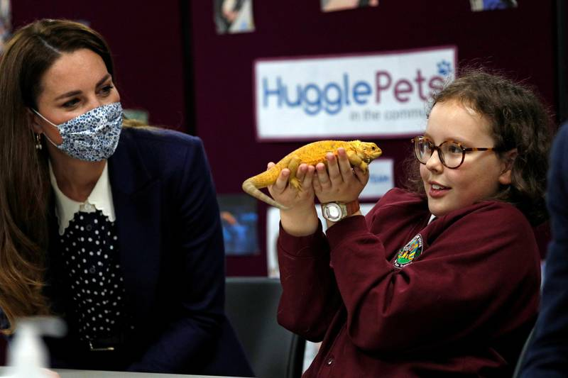 10 year-old Anya Southall handles a chameleon as Britain's Catherine, Duchess of Cambridge looks on, as the Duchess joins  a group of local school children from Loxdale Primary School in a visit at HugglePets in the Community to mark mental health awareness week in Wolverhampton, Britain May 13, 2021. Adrian Dennis/Pool via REUTERS