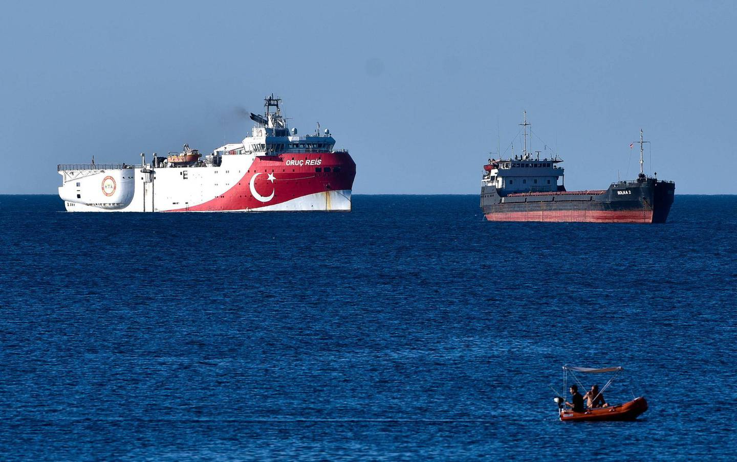 """In this photograph taken from the Mediterranean shores near the city of Antalya, Turkey, a merchant ship, top right, sails past the research vessel Oruc Reis, Thursday, July 23, 2020. Greece has warned Thursday it will do """"whatever is necessary"""" to defend its sovereign rights in response to plans by neighbor Turkey to proceed with an oil-and-gas research mission south of Greek islands in the Eastern Mediterranean. The dispute over seabed mineral rights has led to increased navy deployments by both NATO members in the region, where the Oruc Reis, is being prepared for a survey mission. (Ibrahim Laleli/DHA via AP)"""