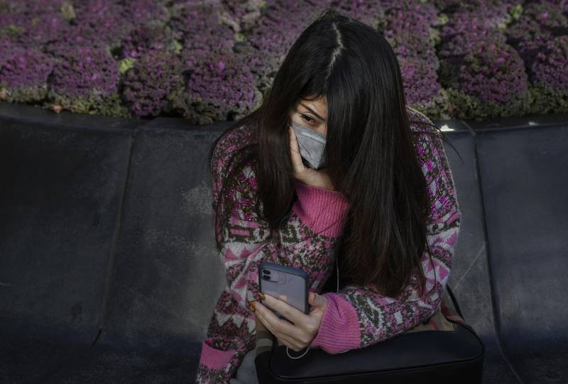 BEIJING, CHINA - MARCH 10: A Chinese woman wears a protective mask as she looks at her phone while sitting in the Sanlitun shopping area on March 10, 2020 in Beijing, China. The number of cases of the deadly new coronavirus COVID-19 being treated in China dropped to below 18,000 in mainland China Sunday, in what the World Health Organization (WHO) declared a global public health emergency last month. China continued to lock down the city of Wuhan, the epicentre of the virus, in an effort to contain the spread of the pneumonia-like disease. Officials in Beijing have put in place a mandatory 14 day quarantine for all people returning to the capital from other places in China and countries with a large number of cases like South Korea and Japan. The number of those who have died from the virus in China climbed to over 3140 on Tuesday, mostly in Hubei province, and cases have been reported in many other countries including the United States, Canada, Australia, Japan, South Korea, India, Iran, Italy, the United Kingdom, Germany, France and several others. The World Health Organization has warned all governments to be on alert and raised concerns over a possible pandemic. Some countries, including the United States, have put restrictions on Chinese travellers entering and advised their citizens against travel to China.(Photo by Kevin Frayer/Getty Images)