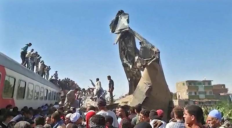 This screengrab provided by AFPTV shows people gathered around the wreckage of two trains that collided in the Tahta district of Sohag province, some 460 kms (285 miles) south of the Egyptian capital Cairo, reportedly killing at least 19 people and injuring scores of others, on March 26, 2021. - Egypt has been plagued with deadly train accidents in recent years that have been widely blamed on inadequate infrastructure and poor maintenance. (Photo by - / AFP)