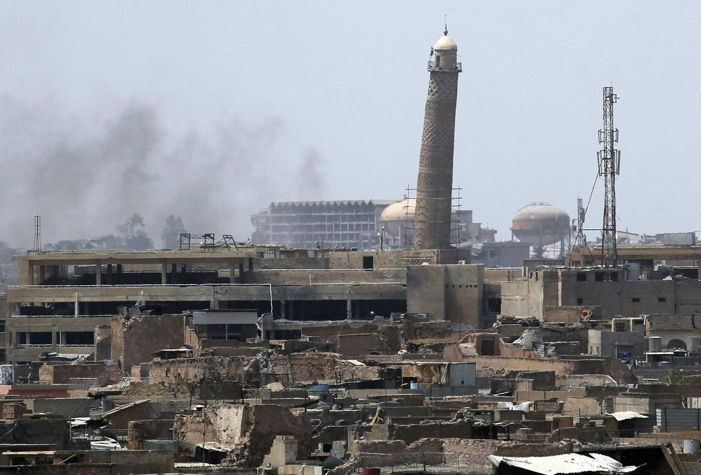 (FILES) This combination of pictures created on January 10, 2018 shows a general view (L) of smoke rising next to the Al-Hadba minaret at the Al-Nuri Mosque in Mosul's Old City on June 18, 2017. AFP