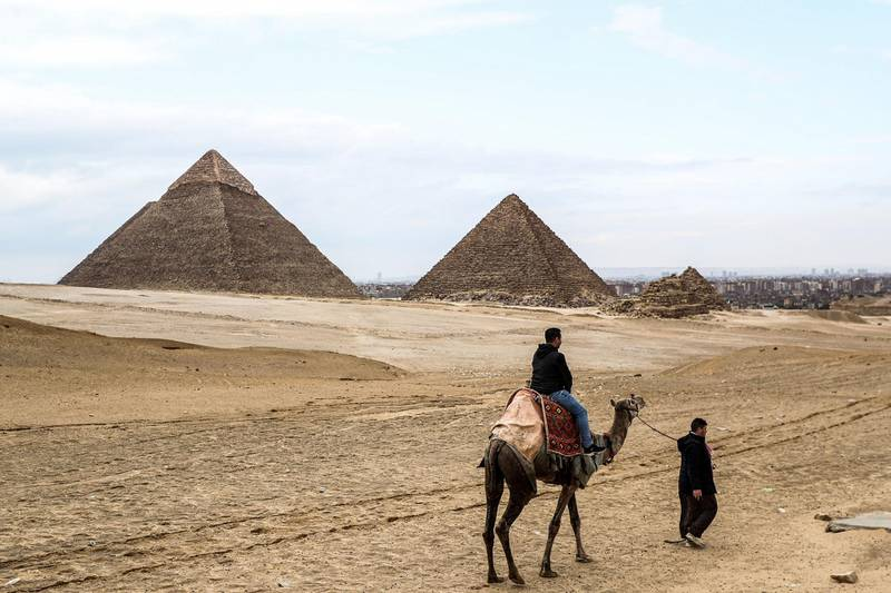A camel guide leads a tourist on a camel at the Giza pyramids plateau overlooking the Giza necropolis on the southwestern outskirts of the Egyptian capital on March 13, 2020, as in the background are seen the Pyramid of Khafre (Chephren) and Menkaure (Menkheres). (Photo by Mohamed el-Shahed / AFP)