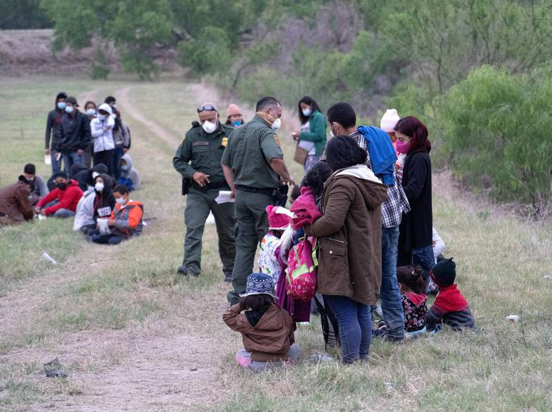 A group of 60 migrants weight in a field as US Border Patrol agents inspect their documents and belongings. Willy Lowry/ The National