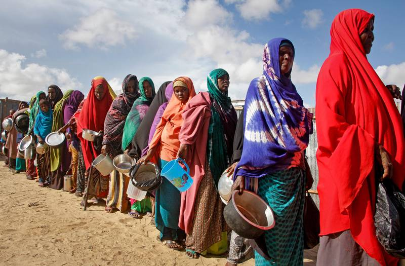 FILE - In this Saturday, May 18, 2019 file photo, newly-arrived women who fled drought line up to receive food distributed by local volunteers at a camp for displaced persons in the Daynile neighborhood on the outskirts of the Somalian capital Mogadishu. On Tuesday, June 5, 2019, a United Nations emergency relief coordinator said more than 2 million men, women and children could die of starvation in Somalia by summer's end if international aid is not sent quickly to the drought-stricken African country. (AP Photo/Farah Abdi Warsameh)