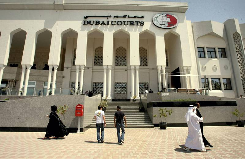 Pedestrians walk past Dubai's courts building during a hearing on April 04, 2010 in the case of a British couple sentenced to a month in jail after being convicted of kissing in public in a restaurant in the Muslim Gulf emirate. The couple's lawyer said the appeals court upheld the one-month prison sentence against the two, named by the British press as Ayman Najafi, 24, a British expat, and tourist Charlotte Lewis, 25. The couple were arrested in November 2009, after they were accused of consuming alcohol and kissing in a restaurant in the trendy Jumeirah Beach Residence neighbourhood.     AFP PHOTO/STR / AFP PHOTO
